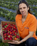 Natalia Peres, UF/IFAS associate professor of plant pathology, shows a container of strawberries.