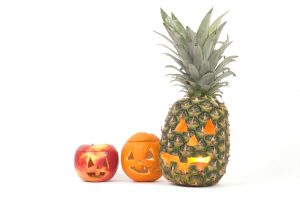 jack o lanterns made-from-pineapple-apple-and-orange-creating-tropical-halloween-decoration